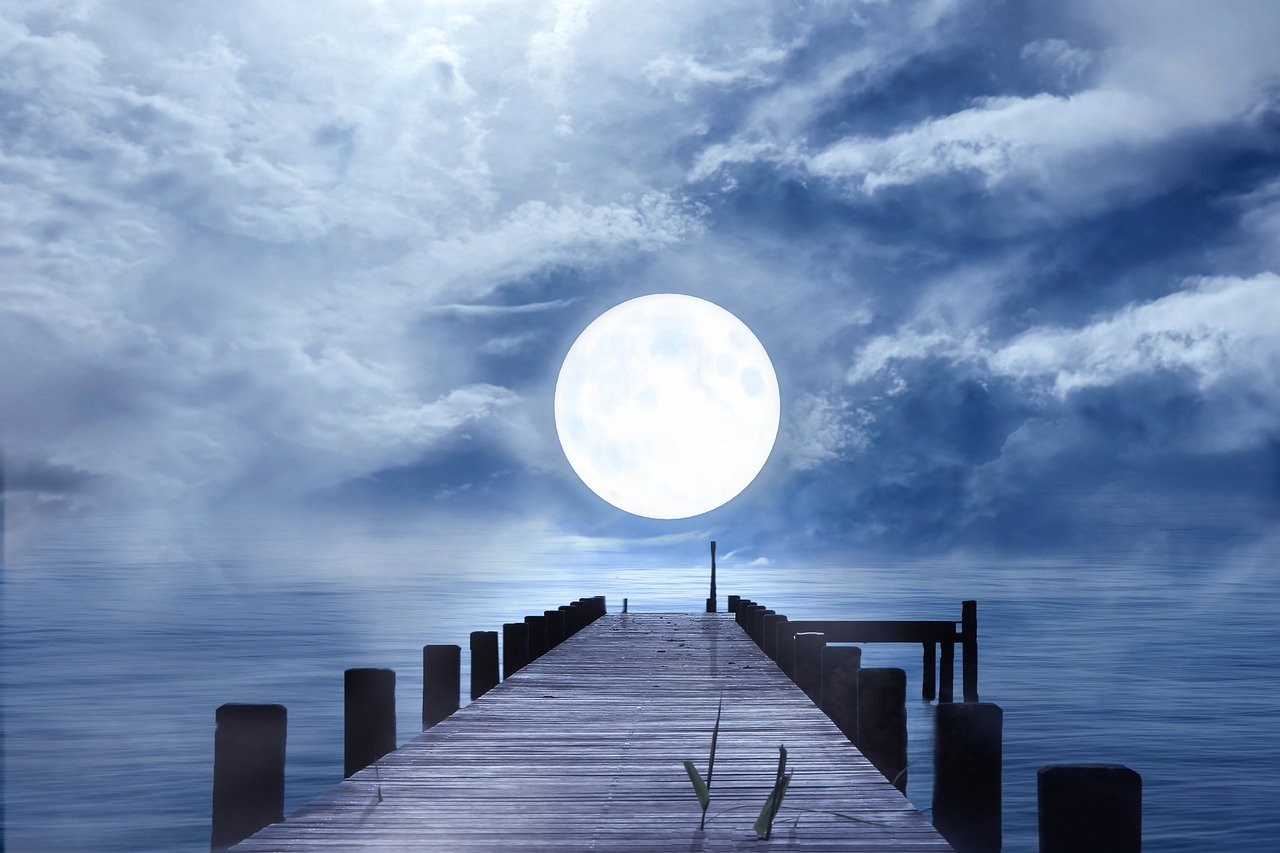 Volle maan boven een steiger in het water